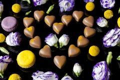 Corazón de los chocolates con leche rodeado con las flores del lado en negro Fotos de archivo libres de regalías