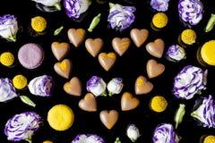 Corazón de los chocolates con leche rodeado con las flores desde arriba en negro Fotos de archivo libres de regalías