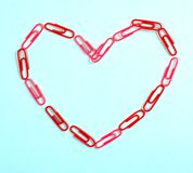 Corazón de los clips de papel de la oficina en un fondo azul imagen de archivo