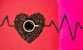 Corazón de los granos de café y un histograma en un fondo rojo y rosado foto de archivo