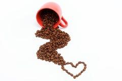 Corazón de los granos de café de una taza volcada. Fotos de archivo