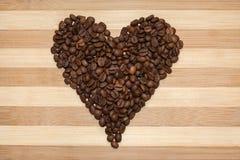 Corazón de los granos de café en el tablero de madera Fotos de archivo