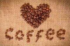 Corazón de los granos de café en harpillera Fotos de archivo