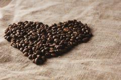 Corazón de los granos de café en horizontal de lino Imágenes de archivo libres de regalías