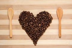 Corazón de los granos de café y de las cucharas de madera Fotos de archivo libres de regalías