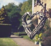 Corazón de los palillos que cuelgan en la cinta blanca Imagen de archivo