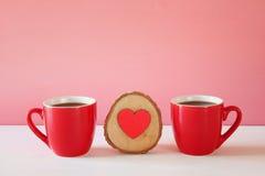 Corazón de madera al lado de las tazas de café en la tabla de madera Fotografía de archivo
