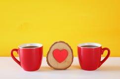 Corazón de madera al lado de las tazas de café en la tabla de madera Fotos de archivo libres de regalías