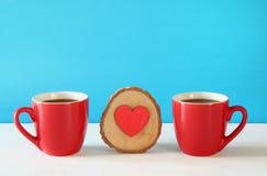 Corazón de madera al lado de las tazas de café en la tabla de madera Foto de archivo