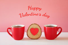 Corazón de madera al lado de las tazas de café en la tabla de madera Imagen de archivo