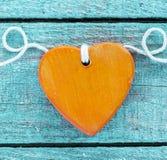 Corazón de madera anaranjado romántico en la madera de la turquesa Imágenes de archivo libres de regalías
