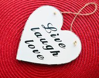 Corazón de madera blanco decorativo con el amor vivo de la risa del lema en fondo rojo de la servilleta de la paja Vivo, risa, am Fotografía de archivo