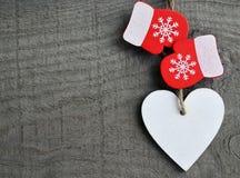 Corazón de madera blanco decorativo de la Navidad y manoplas rojas en fondo de madera rústico gris con el espacio de la copia Foto de archivo libre de regalías