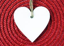 Corazón de madera blanco decorativo en servilleta roja de la paja con el espacio de la copia Fotos de archivo libres de regalías