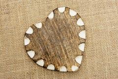Corazón de madera con el borde blanco en la arpillera Imágenes de archivo libres de regalías
