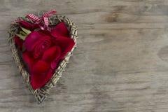 Corazón de madera con Rose y los pétalos Imagen de archivo libre de regalías