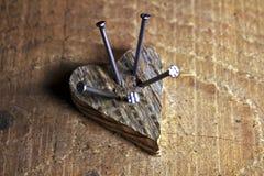 Corazón de madera del amor perforado por los nailes Imagenes de archivo
