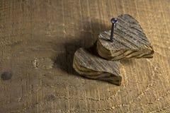 Corazón de madera dos clavado en fondo de madera Foto de archivo libre de regalías