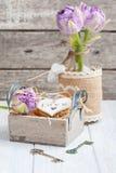 Corazón de madera en caja de regalo del vintage con los tulipanes dominantes y púrpuras Imagen de archivo