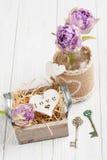 Corazón de madera en caja de regalo del vintage con los tulipanes dominantes y púrpuras Fotografía de archivo