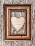 Corazón de madera en marco en la madera vieja imagen de archivo