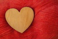 Corazón de madera en un fondo de hilos de lana rojos Fotos de archivo libres de regalías