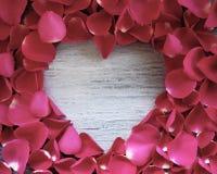 Corazón de madera rodeado por los pétalos color de rosa fotografía de archivo libre de regalías