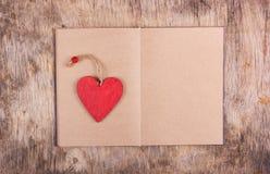 Corazón de madera rojo y un libro abierto con las páginas en blanco en el viejo fondo de madera Señales y tarjeta del día de San  Foto de archivo libre de regalías