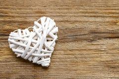 Corazón de mimbre blanco en fondo de madera marrón Imagen de archivo