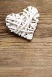 Corazón de mimbre blanco en fondo de madera marrón Fotografía de archivo