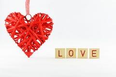 corazón de mimbre rojo hermoso con un fondo blanco con amor de la inscripción de las letras Imágenes de archivo libres de regalías
