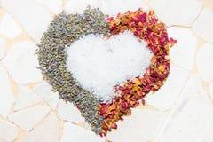 Corazón de pétalos color de rosa, de la lavanda y de cristales del baño Imagen de archivo