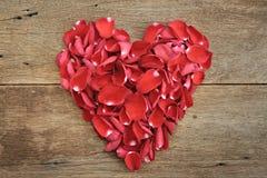 Corazón de pétalos color de rosa rojos en de madera El día de tarjeta del día de San Valentín, aniversario Fotos de archivo