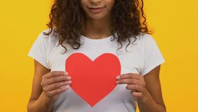 Corazón de papel que se sostiene moreno rizado, compartiendo amor y cuidado, concepto de la caridad almacen de video