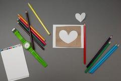 Corazón de papel rodeado con las fuentes de escuela fotografía de archivo