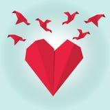 Corazón de papel rojo de la papiroflexia con los pájaros de la papiroflexia del vuelo en fondo de la pendiente Fotos de archivo libres de regalías