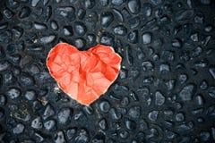 Corazón de papel rojo en el piso de la piedra del guijarro imágenes de archivo libres de regalías