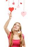 Corazón de papel rojo y rosado de la mujer del diseñador sonriente de los touchs de la tarjeta del día de San Valentín Imagen de archivo