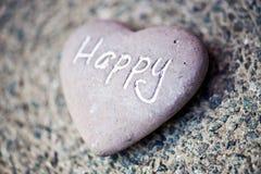 Corazón de piedra con la palabra - feliz Foto de archivo