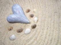 Corazón de piedra en la arena y las cáscaras grises - foco selectivo Imagen de archivo libre de regalías