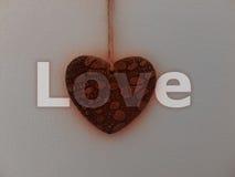 Corazón de piedra que brilla intensamente rojo en la pared blanca - AMOR Foto de archivo libre de regalías
