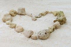 Corazón de piedras en la arena Imágenes de archivo libres de regalías