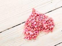 Corazón de piedras rosadas en los tableros blancos Fotografía de archivo