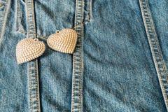Corazón de plata adornado en los vaqueros para el fondo Foto de archivo