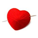 Corazón de punto de la bola con una aguja aislada en blanco Fotos de archivo