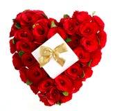 Corazón de rosas rojas con el regalo y el arqueamiento de oro Imagenes de archivo