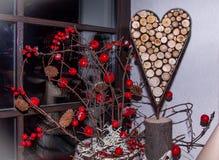 Corazón decorativo del fondo de los anillos de las ramas de árbol rodeadas por las bayas rojas brillantes foto de archivo libre de regalías