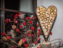 Corazón decorativo del fondo de los anillos de las ramas de árbol rodeadas por las bayas rojas brillantes fotos de archivo libres de regalías