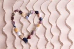 Corazón decorativo del guijarro en la arena de oro de la playa Fotos de archivo libres de regalías