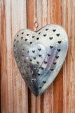 Corazón decorativo del metal en la pared de madera Fotografía de archivo